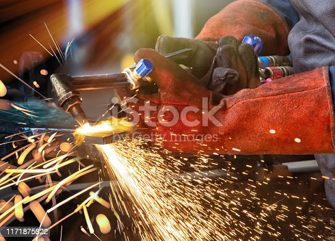 african man with a cutting torch in a factory working