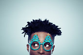 Close up of african man wearing christmas tree shaped glasses looking away on gray background.
