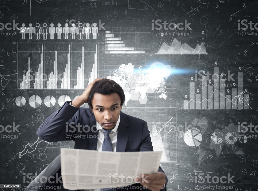 African man with newspaper, graphs and map stock photo