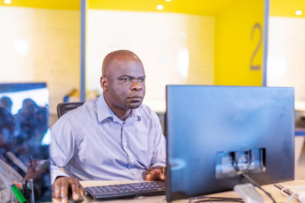 African Man With Sight Problems Working at a Computer stock photo