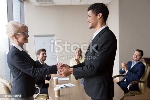 923041456 istock photo African manager holding hand of successful caucasian worker express respect 1129629320