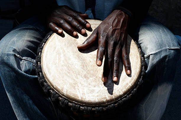 African man's hands playing a drum between his legs stock photo
