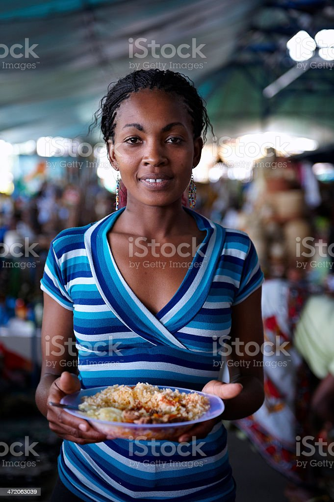 Young woman looking at camera, eating while working at a street...