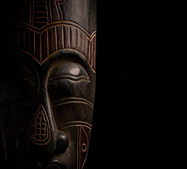 afrikanischer maske auf schwarzem hintergrund - afrikanische masken stock-fotos und bilder