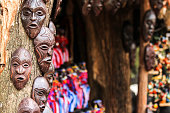 African masks and curios fixed onto a tree for sale in Nairobi at a road side curion market