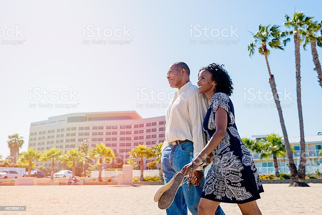 African mature couple in love walking on the beach stock photo