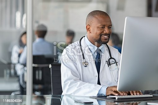 Practitioner typing on computer in modern clinic. Doctor at work in office using computer with copy space. African happy specialist wearing white coat and sitting at desk while mediacal team having meeting in background.