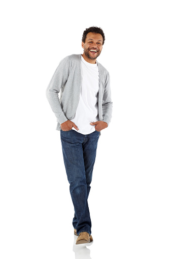 Full length portrait of handsome african man standing in casuals with his hands in pocket looking at camera smiling over white background
