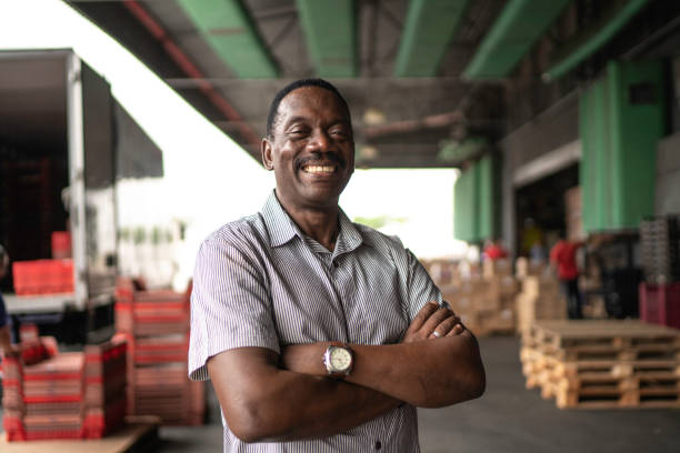 African mature man owner portrait at warehouse African mature man owner portrait at warehouse brazilian ethnicity stock pictures, royalty-free photos & images