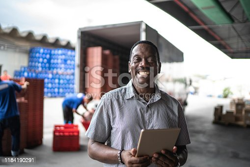 African mature man owner using digital tablet at warehouse portrait