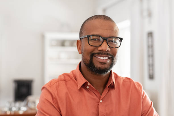 African mature man with spectacles Smiling mature man wearing spectacles looking at camera. Portrait of black confident man at home. Successful entrepreneur feeling satisfied. men stock pictures, royalty-free photos & images