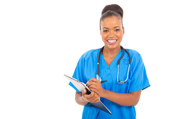 african medical doctor writing on clipboard pasante - foto de stock