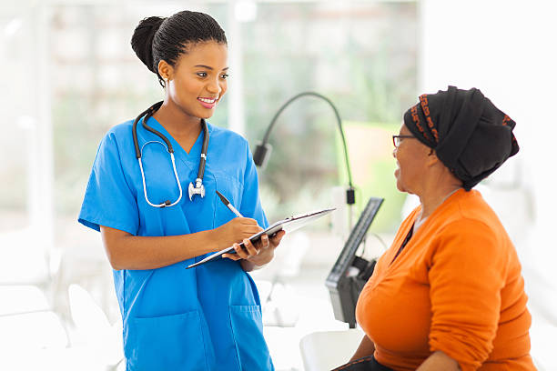 african medical nurse and senior patient stock photo