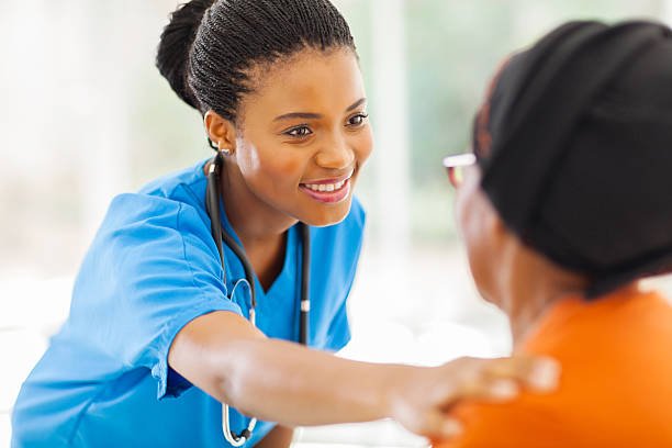 african medical nurse comforting senior patient stock photo
