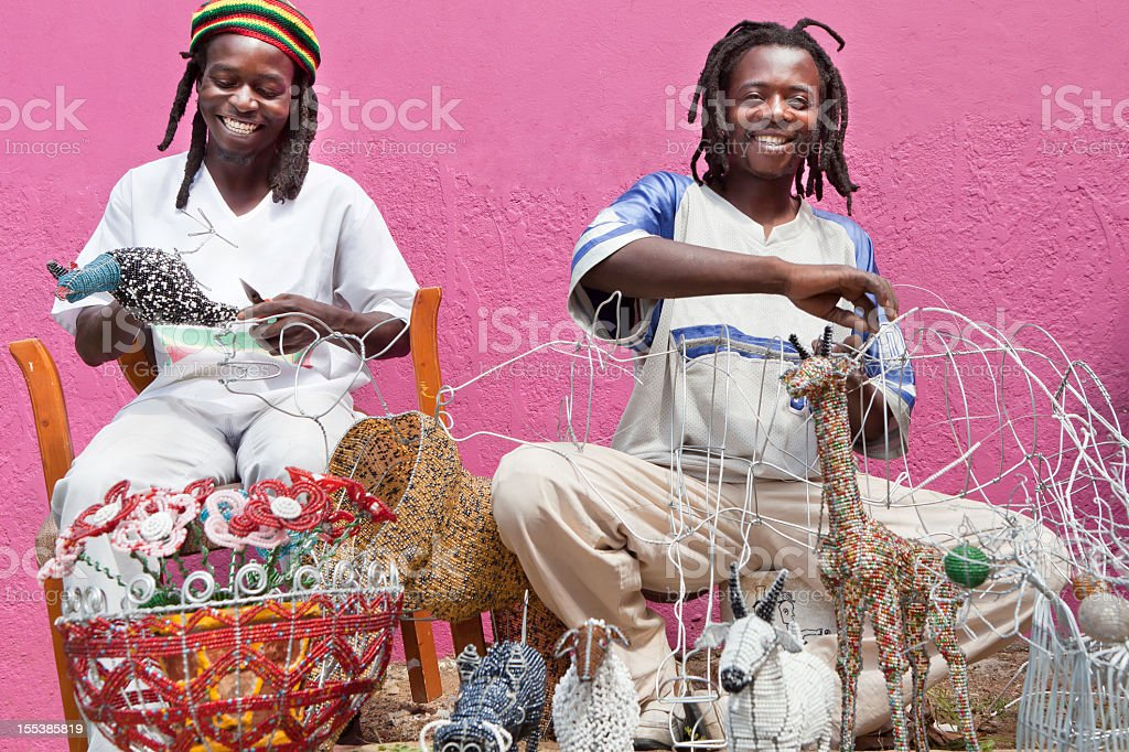 African men designing and producing beadwork stock photo
