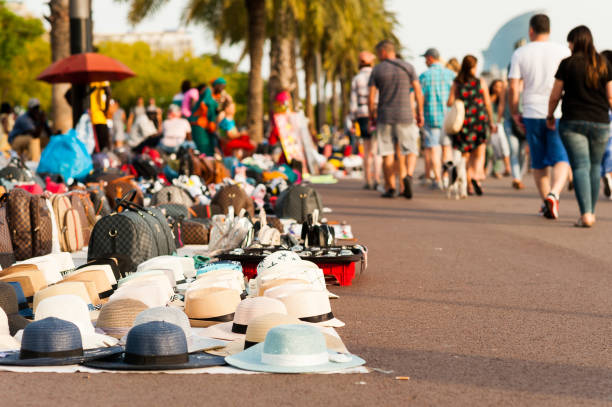 """african migrants street vendors called """"manteros"""" sell counterfeit goods along sidewalk at sunset with tourists walking by in the barcelona port stock photo"""