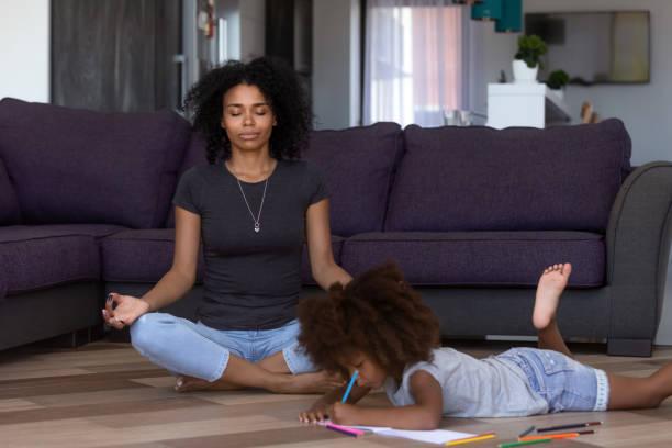 mãe africana fazendo yoga enquanto filha criança desenho no chão - consciencia negra - fotografias e filmes do acervo