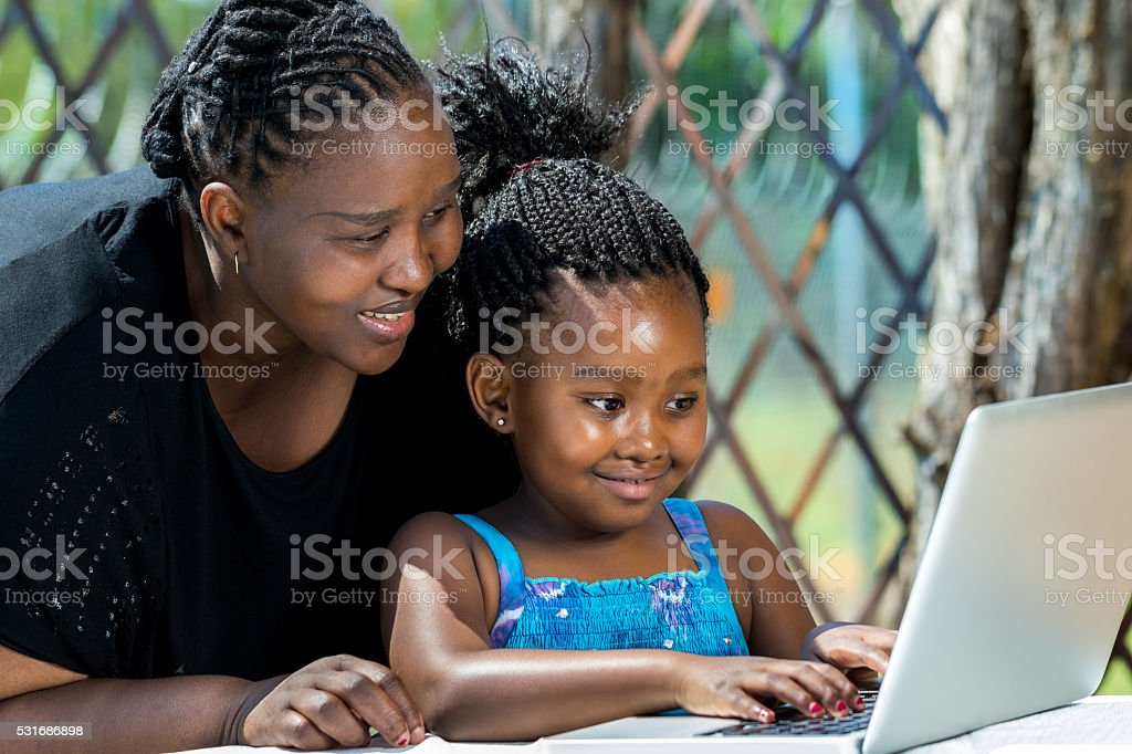 African mother and child looking at laptop outdoors. stock photo