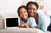 istock African mother and daughter recommending useful app 1190130081