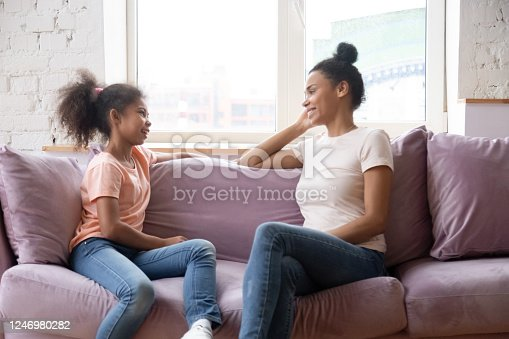 1070262182 istock photo African mother and daughter talking sitting on couch at home 1246980282