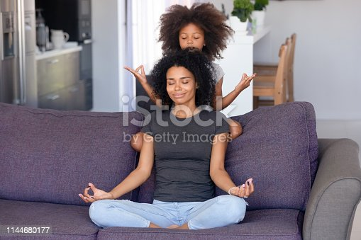 istock African mother and little daughter meditating on couch at home 1144680177