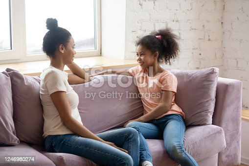 1070262182 istock photo African mother and pre-teen daughter talking seated on couch 1246980274