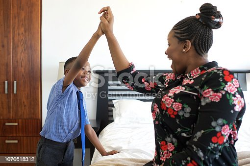 An African mother dressing her son and doing his tie for school moments high-five indoors Strand Cape Town South Africa