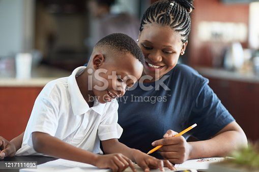 South African mother in late 20s smiling with her 6 year old son as they work together on his writing and drawing skills.