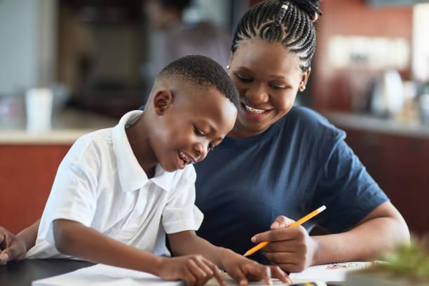 afrikanische mutter und junger sohn verbringen kreative zeit zusammen - homeschooling stock-fotos und bilder