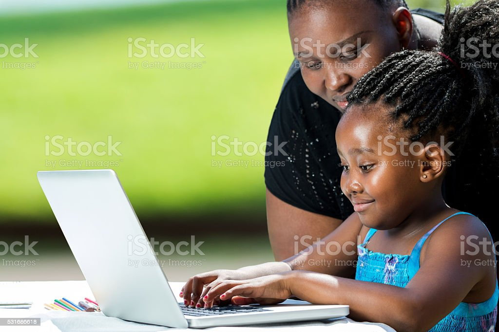African mother helping kid on laptop. stock photo