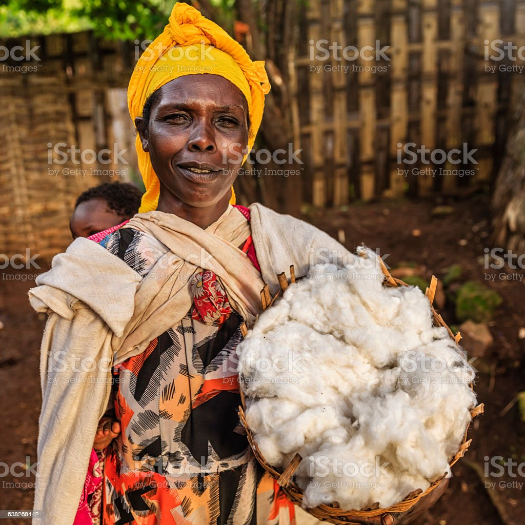 African mother holding basket of wool, East Africa stock photo