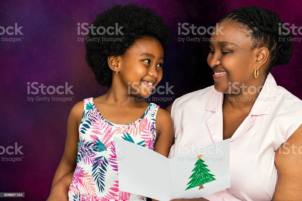 African mother reading christmas card to little girl. stock photo