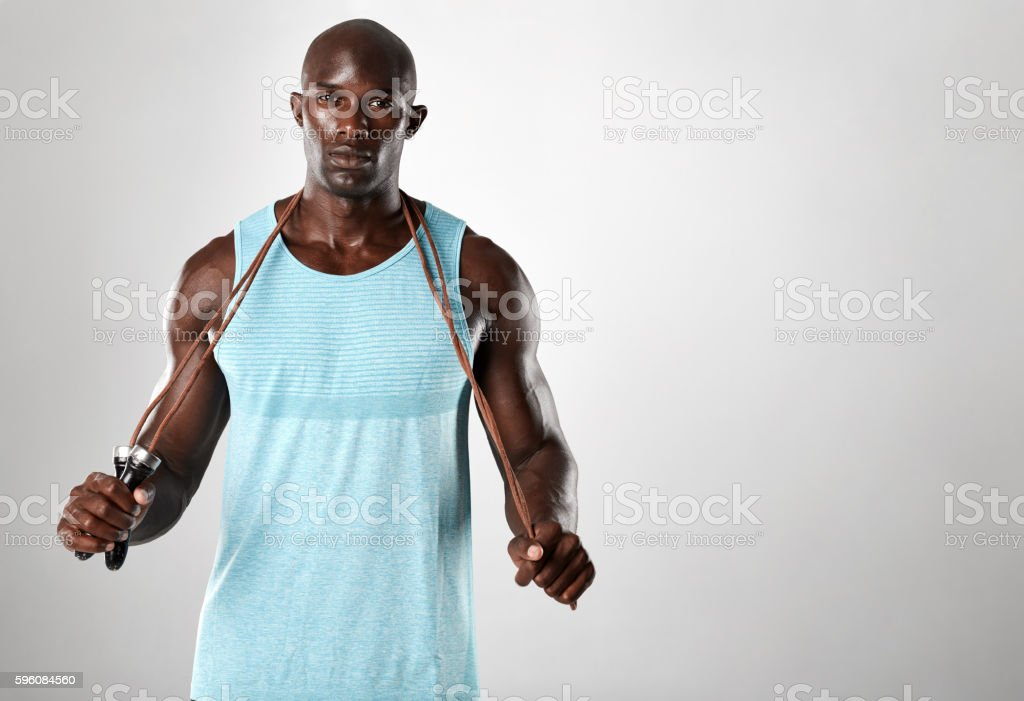 African muscular man posing with jumping rope stock photo