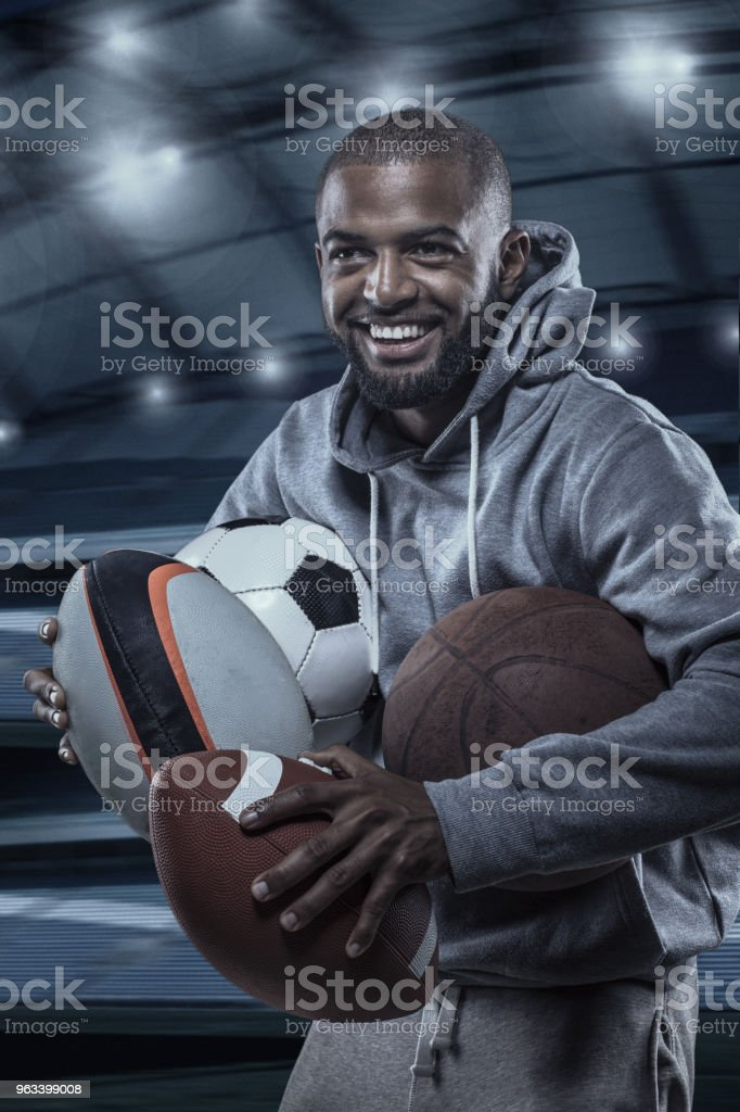 African Muslim Non-Caucasian Athlete holding a selection of sports balls in a floodlit stadium - Zbiór zdjęć royalty-free (Afroamerykanin)