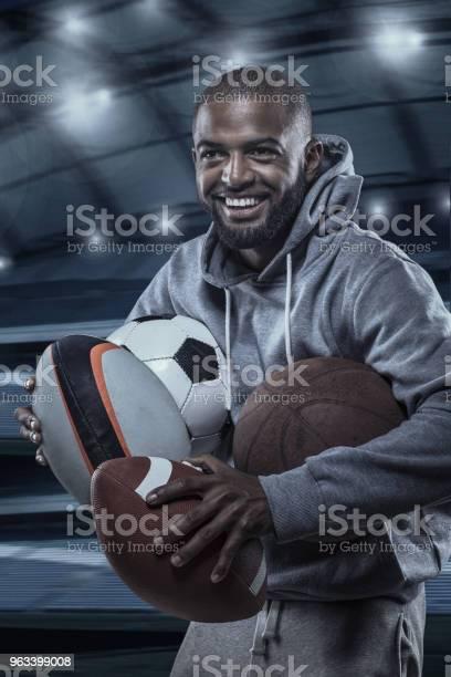Afrykański Muzułmanin Niekaukaski Sportowiec Posiadający Wybór Piłek Sportowych Na Oświetlonym Stadionie - zdjęcia stockowe i więcej obrazów Bluza z kapturem