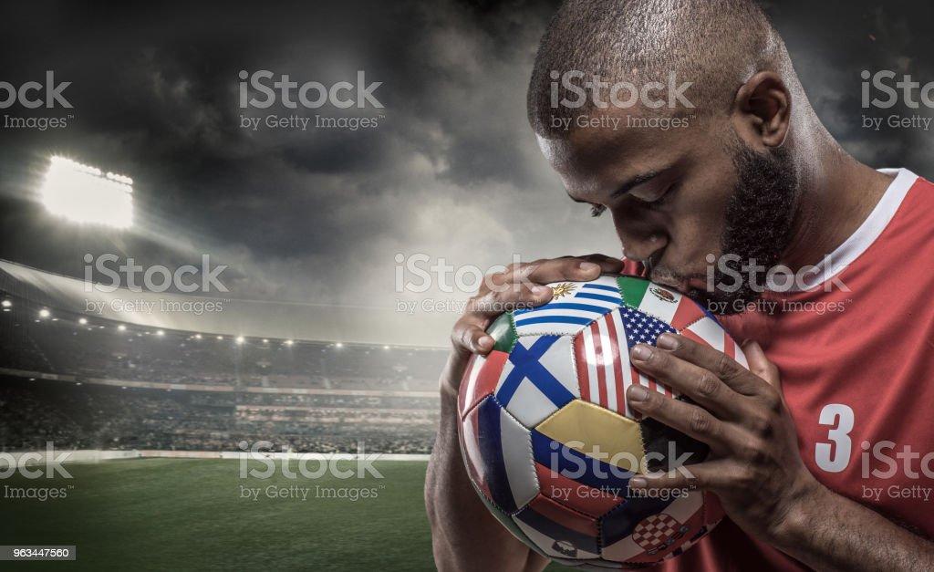 Işıklandırılmış bir stadyumda futbol topu Afrika Müslüman Non-Kafkas futbolcu bir bayrak ile kaplı - Royalty-free Afrika Kökenli Amerikalılar Stok görsel