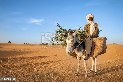 African nomad senior having protection in face. He is crossing the dry desert and riding his donkey during warm day.