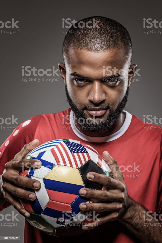 African Non-Caucasian Football Player Holding a flag covered Soccer Ball in studio shot royalty-free stock photo