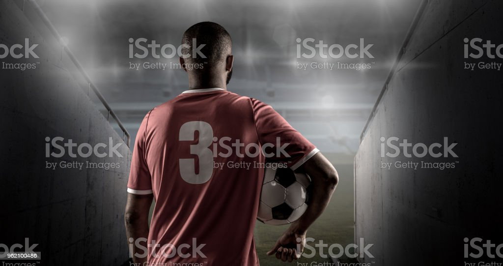African Non-Caucasian Football Player Holding a Soccer Ball in front of Stadium Lights stock photo