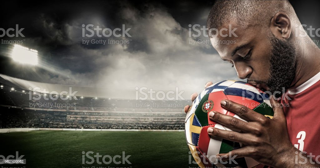 African Non-Caucasian Football Player kissing a Soccer Ball in front of Stadium Lights stock photo