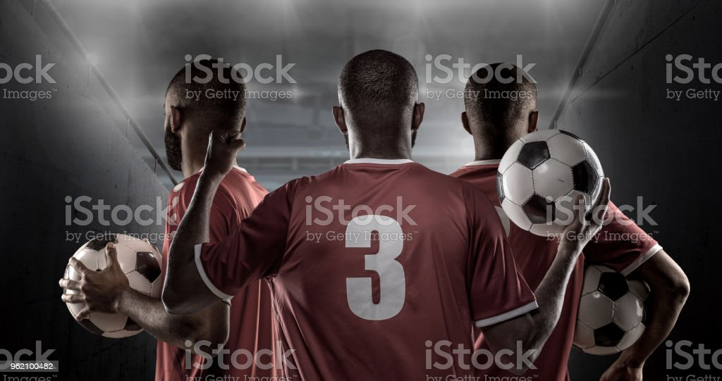 3 African Non-Caucasian Football Players Holding a Soccer Ball in front of Stadium Lights stock photo