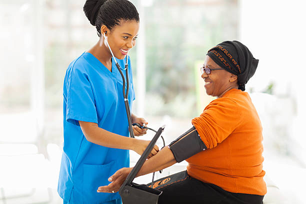 african nurse checking senior patient's blood pressure stock photo