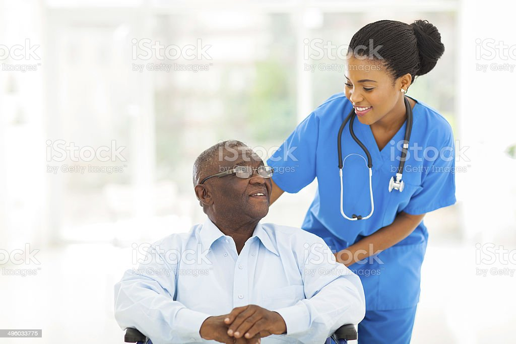 african nurse taking care of senior patient in wheelchair stock photo