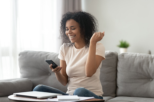 istock African overjoyed woman holding smartphone looking at screen celebrating achievement 1186418493