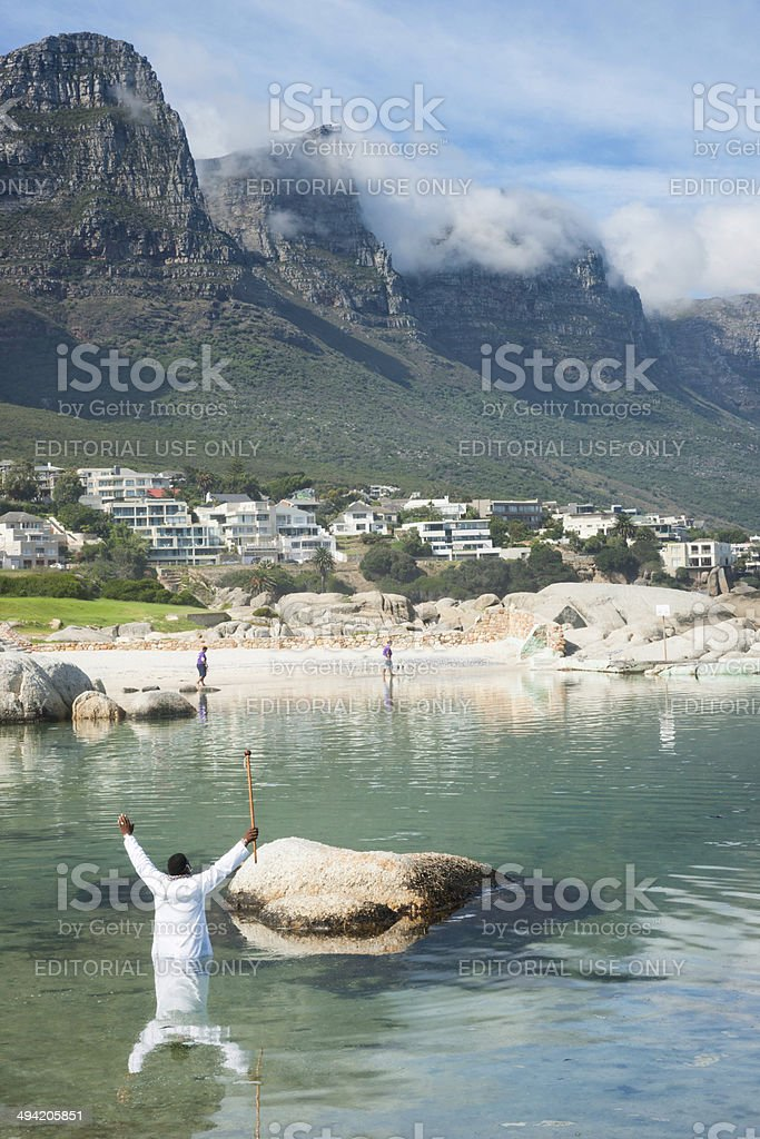 African pastor rejoices over ocean baptisms stock photo