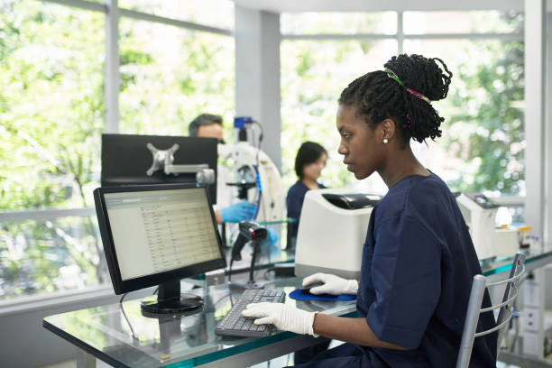 African Pathology Technician Working on Computer in Lab stock photo