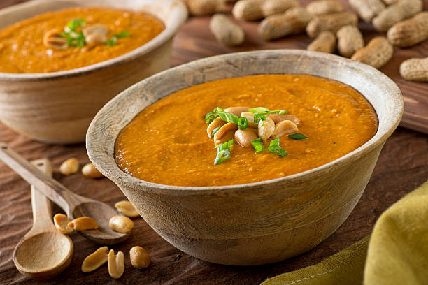 African Peanut Soup A delicious bowl of homemade african peanut soup with green onion garnish. stew stock pictures, royalty-free photos & images