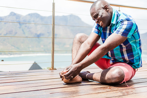 An African person gripping his big toe, maybe he is having gout. Image taken with Canon 5 DS.