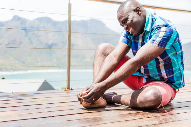 African person gripping his big toe having gout stock photo