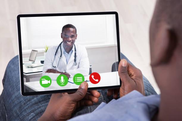 persona africana sentada con tableta digital - telehealth fotografías e imágenes de stock